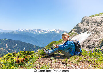 A boy traveler with trekking poles and a backpack is resting in the summer on top of a mountain with snow.