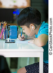 A boy using cellphone and painting on a white paper at home