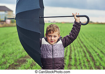 A boy walks on an autumn day in the field with umbrella