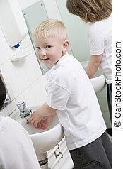 A boy washing his hands in a primary school bathroom