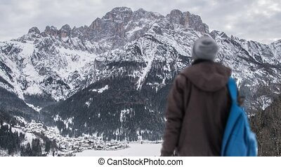 A boy watching the mountains covered with snow