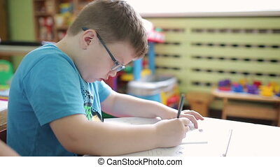 A boy wearing glasses in elementary school writes in pencil...