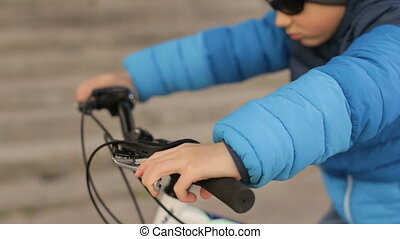 A boy wearing sunglasses sits on a bicycle.Full hd video - A...