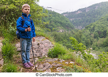 A boy with a backpack and trekking poles stands on a stone rock at the beginning of a mountain gorge