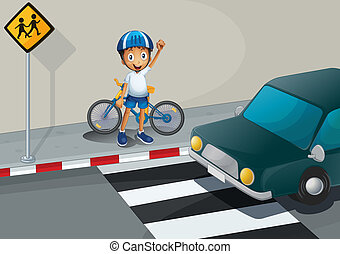 A boy with a bike standing near the pedestrian lane -...