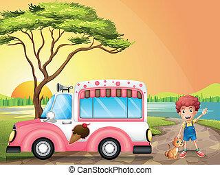 A boy with a cat beside an icecream truck