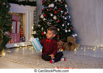 a boy with a gift for new year Christmas tree winter holiday