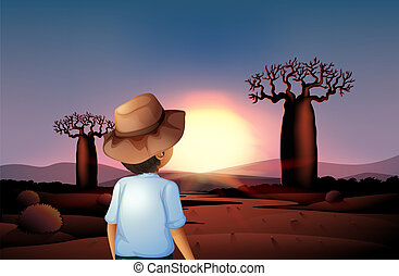 A boy with a hat watching the sunset in the desert