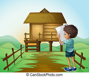 A boy with a paper in front of the nipa hut