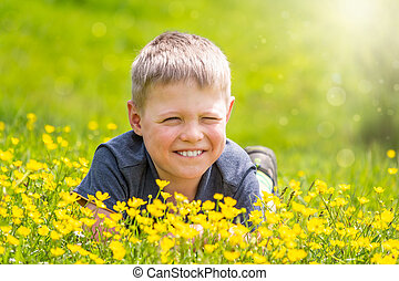 A boy with a smile is resting on a green lawn with yellow wildflowers and squinting from the sun.