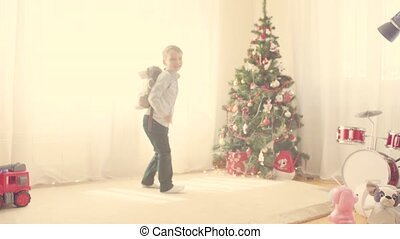 A boy with a toy bag near Christmas tree