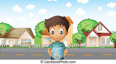 A boy with an aquarium standing across the neighborhood