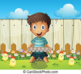 A boy with an empty egg tray and the little chicks