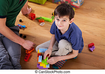 A boy with blocks on the floor