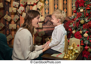 Boy with Cochlear Implants play with Christmas Bell with his Mother