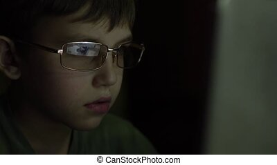 The boy plays computer games. Reflections of a computer monitor in glasses. Computer game addiction. Infatuated with a network game child.