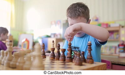 A boy with glasses plays chess. He is sitting at the table ...