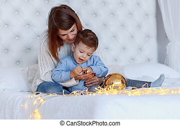 A boy with his mom in front of the christmas tree. happiness and big family concept