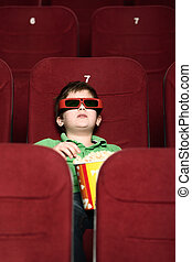 A boy with popcorn at the cinema