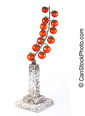 A branch of ripe cherry tomatoes on a pedestal on a white background