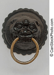 A brass handle with a image of animal (tiger) on the white door