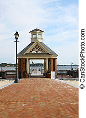 A brick walkway through a large Gazebo leading to the waterfront pier and boat dock landing along the riverwalk landing in Yorktown Virginia
