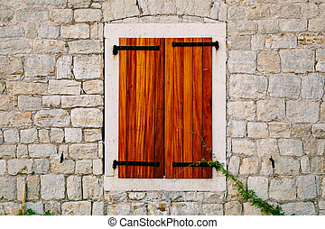 A brick wall with a window opening and new wooden shutters.