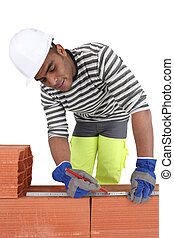 A bricklayer using a ruler