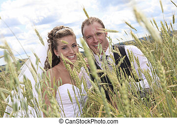 A bride and groom near hay field
