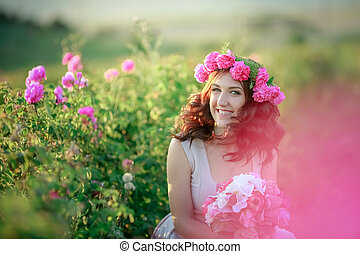 A bride in a white dress holds a bouquet of roses and callas on the background of green grass.