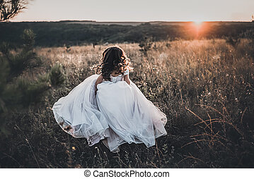 A bride in a white wedding runs across an overgrown field at sunset