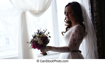 A bride of incredible beauty holding bridal bouquet at her...