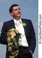 bridegroom - a bridegroom is standing with flowers