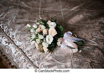 a bride's bouquet lies on the bed