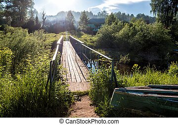 A bridge across a small river in the village in the sun rays