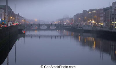 Wide shot of the Dublin canal in a foggy night, with buildings on either side and people walk over it