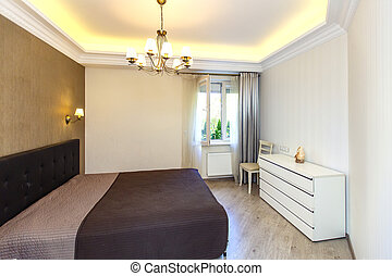 A bright Bedroom with a large double bed with a brown bedspread. Built-in wardrobe, nightstand, ceiling with lighting. Brown Wallpaper inserts