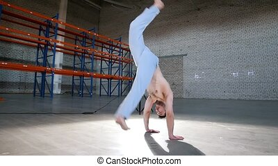 A bright room. An athletic man training his capoeira skills...