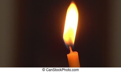 A bright yellow and orange flame of a wax candle in a dark...