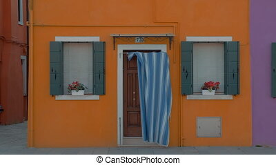 A bright yellow facade of a small house in Burano, Italy....
