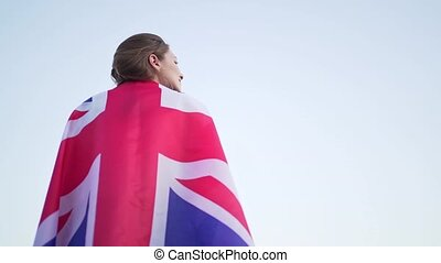 A British woman stands with the national flag on her back and looks into the distance. British independence, female patriot in a free country.