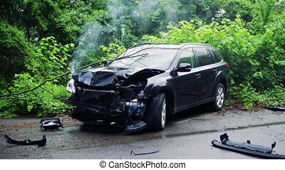 A broken car after an accident, smoke coming out from under...
