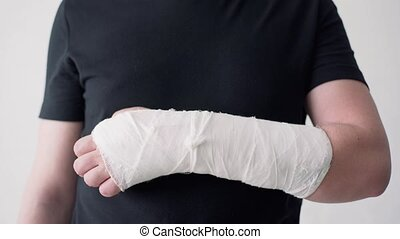 A broken hand in a gypsum bandage. Man tries to bend his ...