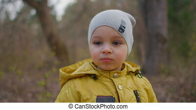 A brooding boy of 2 years in the forest looks at the camera. Charming cute boy with big eyelashes. A boy in a yellow jacket and hat