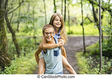 brother and sister giving piggyback in forest