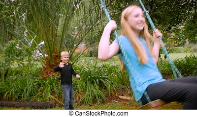 A brother pushes his sister on a swing outside in a park -...