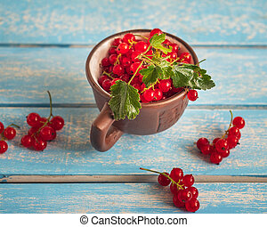 A brown mug full of red currants stands on a blue tray