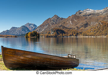 brown rowboat on a mountain lake in the Engadine Valley in Switzerland