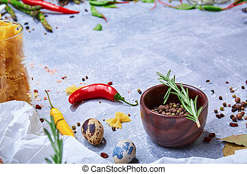A brown wooden bowl with colorful seasoning on a gray background. Spices with hot colorful pepper, bay leaves and a rosemary twig.