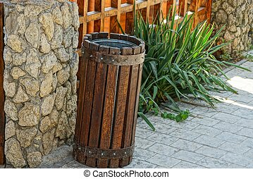 a brown wooden urn stands on the sidewalk against a green grass wall
